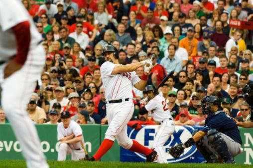 Boston Red Sox batter completing swing at Fenway Park.
