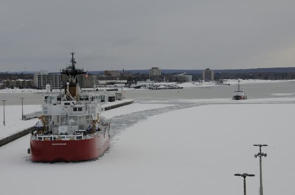 Pictured here with her fleet mate Biscayne Bay (right), the U.S. Coast Guard cutter Mackinaw backs into the lower Poe Lock approach leaving a trail of broken ice at the Soo Locks in Sault Ste. Marie, Mich. March 13, 2013.