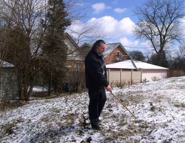 City inspector Ken Kenitz checks what may be an abandoned rat colony dug into a small mound on a vacant lot.