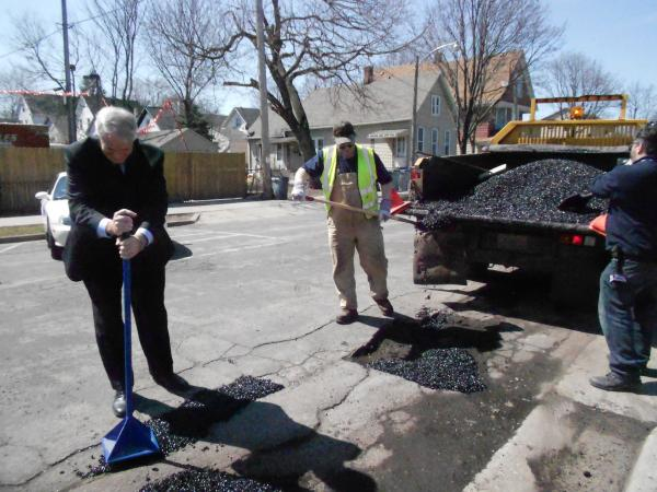 Milwaukee Mayor Tom Barrett helps fill a pothole
