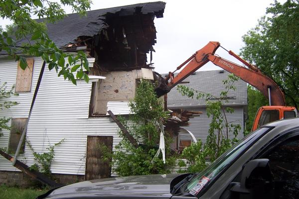 A crane demolishes an abandoned home Wednesday in Milwaukee's central city.