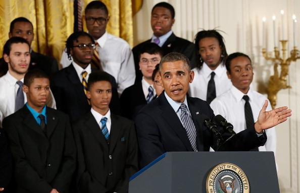 """WASHINGTON, DC - FEBRUARY 27: U.S. President Barack Obama speaks as young men who participate in the 'Becoming A Man' program in Chicago watch him during an event in the East Room of the White House February 27, 2014 in Washington, DC. Obama signed an executive memorandum following remarks on the """"My Brother's Keeper""""initiative."""
