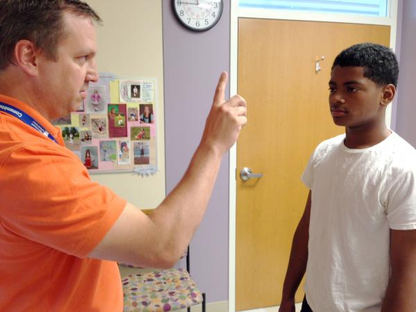 Dr. Kevin Walter, a pediatrician at Children's Hospital, runs through a few neurological tests with 13-year-old Vince Segura, who suffered a concussion playing basketball.