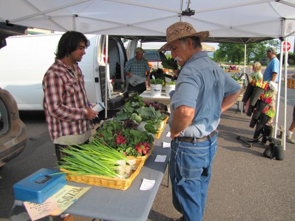 Spickerman mentored the young farmer (far left) for four years; now they sell their vegetables side by side at the farmers market.