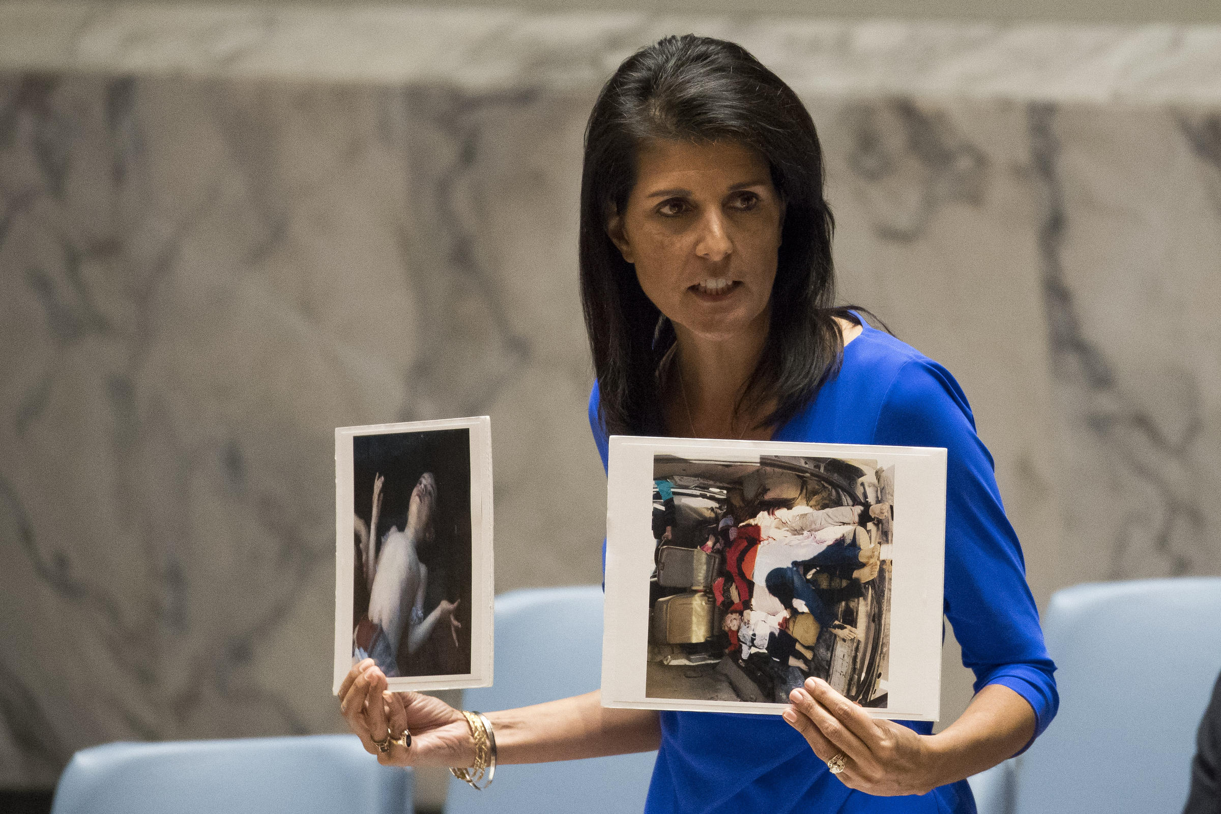 essay poison gas accusations greatly raise syria stakes  u s ambassador to the united nations nikki haley holds up photos of victims of the syrian
