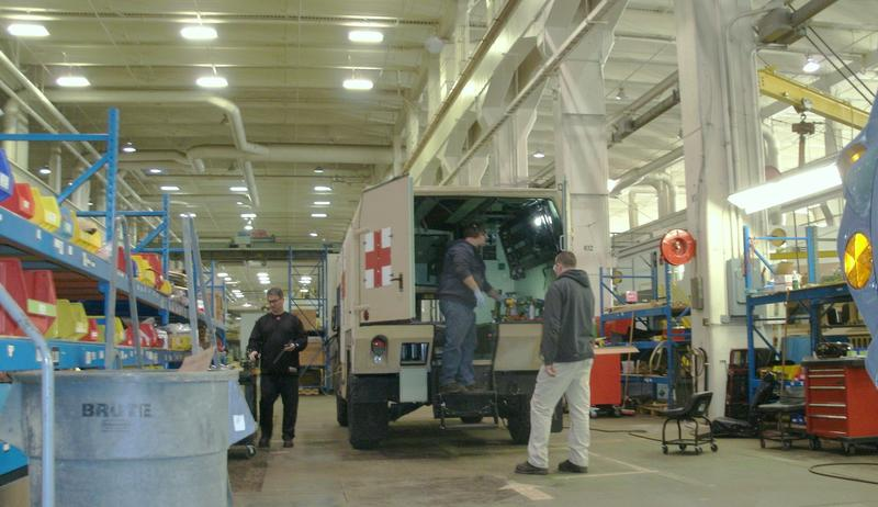 JMTC employees install an ambulance kit on a humvee. (file)