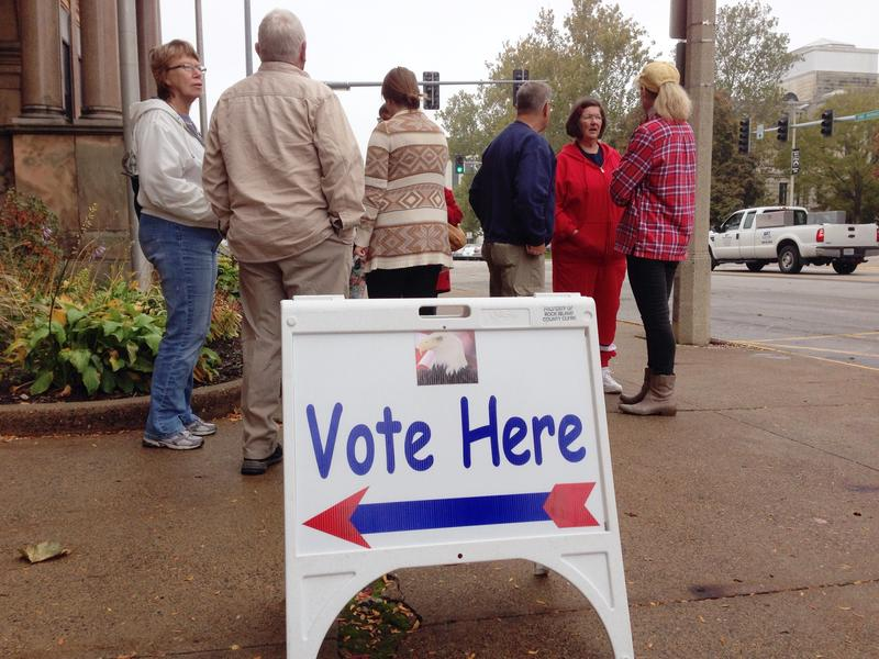 A group of voters talk in front of the Rock Island County building in October, 2014.