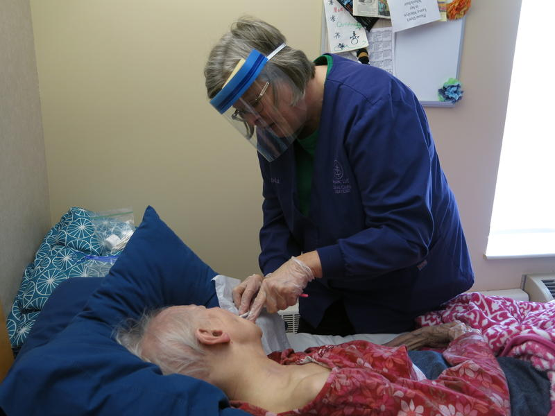 Hygienist, Linda Rowe, brushes a patient's teeth.