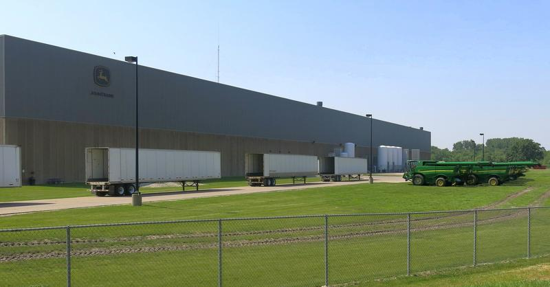 Factory building with farm equipment parked outside