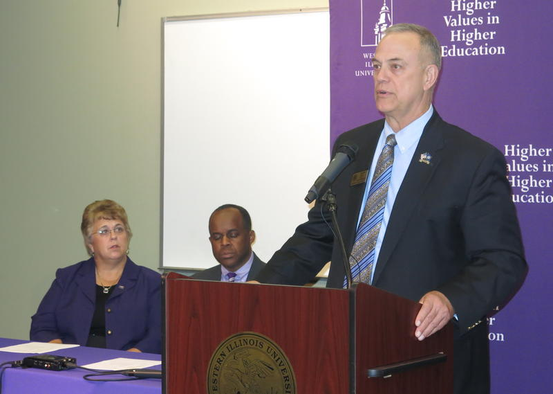 Dir. of WIU's School of Engineering, Bill Pratt, speaks from behind a podium as Pres. Jack Thomas (center) & Interim Provost, Kathleen Neumann, listen while seated.
