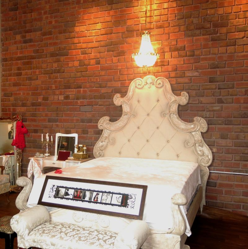A white, ornate bed with upholstered head- and footboards with a small chandelier above and brick wall as a backdrop