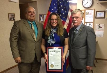 Amy Hess stands between two men and holds the plaque she received as an award from the IL Dept. of Veterans Affairs for going above and beyond the call of duty.
