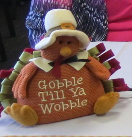 A small, stuffed animal turkey dressed as a pilgrim, with