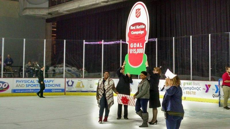Two people hold a large sign depicting a red kettle with $815,000 as goal.