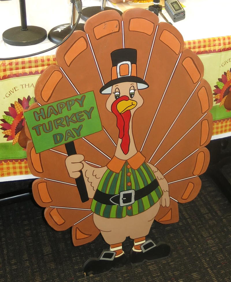 A decoration featuring a turkey with a sign that reads,