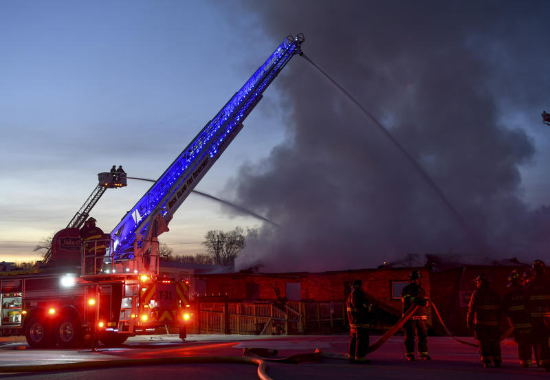 A fire truck sits in front of a building with smoke pouring out of the roof as Rock Island firefighters try to put out a fire at Jake O's Grille on Blackhawk Road in Rock Island.