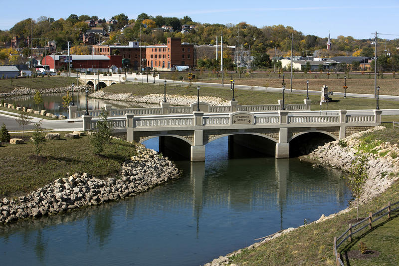 A creek with riprap along the shore with green grass and other landscaping is shown with a bridge and buildings in the background.