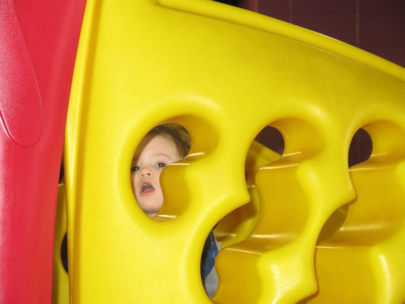 A toddler looks through a small hole in the side of a yellow playground structure.