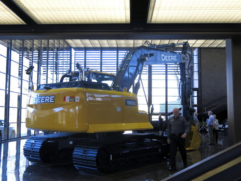 Yellow and black excavator with windows behind it