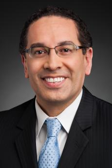 Juan Sepúlveda, PBS Senior Vice President, Station Services, image shows a smiling man with glasses in a dark coat, white shirt & light blue tie.