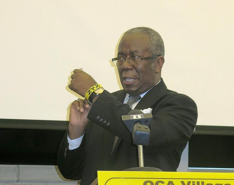 Rev. P. Wonder Harris shows his wristband while talking about the program.