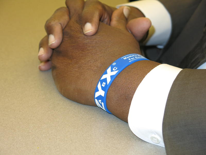 A law enforcement officer's folded hands with a blue and white wristband on his left wrist