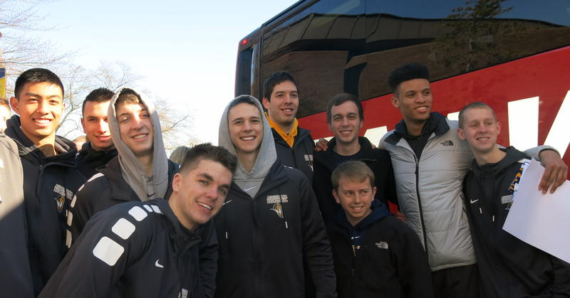 A group of young men smile for pictures while standing beside a red and black bus.