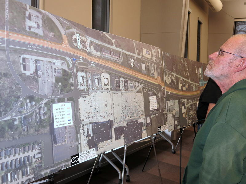 A man with a beard in a green jacket looks at a very large photo and map propped up on an easel.