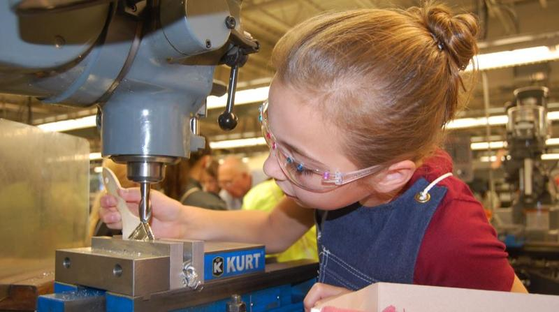 A 8-9 year old girls wearing safety glasses works with a machine and brush.