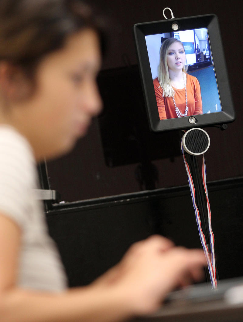 In the foreground, a student in a classroom listens as another student talks via the telepresence robot. It's a wheeled device with a tablet or notebook computer mounted on top. The screen shows the other student's face and torso.