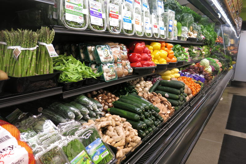 Green, yellow, red and orange vegetables displayed in rows and on shelves