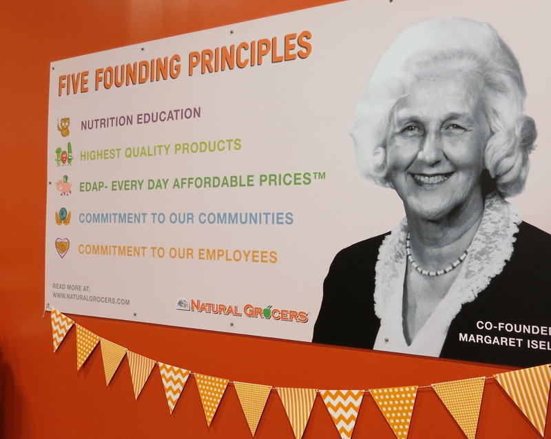 A black and white photo of co-founder, Margaret Isely, is displayed as a large graphic on one wall alongside a list of five founding principles.