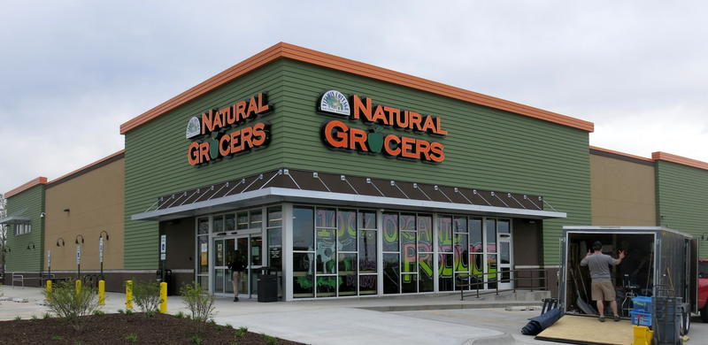 The outside of the store is glass with green walls above with the name in orange. But the