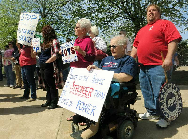 Kathy Doherty of Rock Island protests Governor Rauner to support of state workers Monday, April 17.