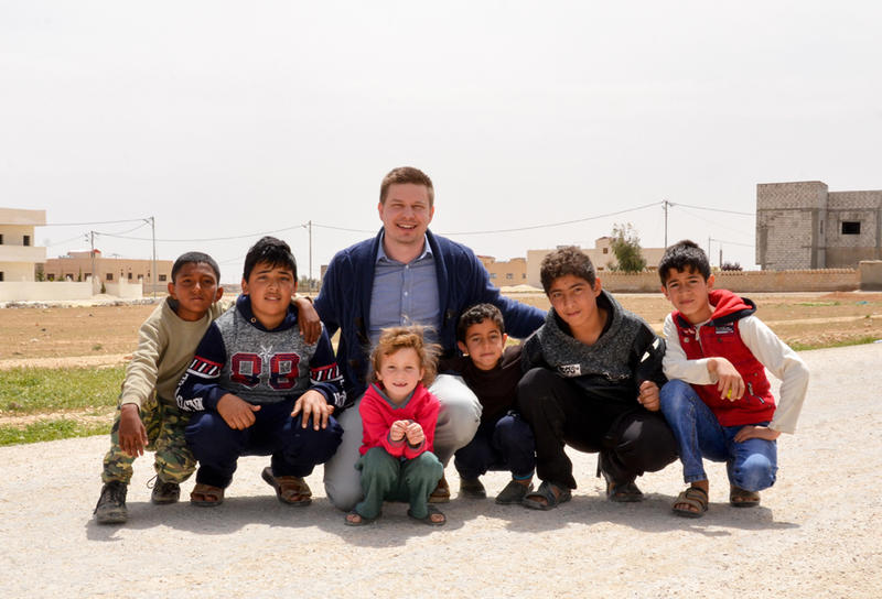 Ethan Anderson poses with local Syrian children in Mafraq, Jordan.
