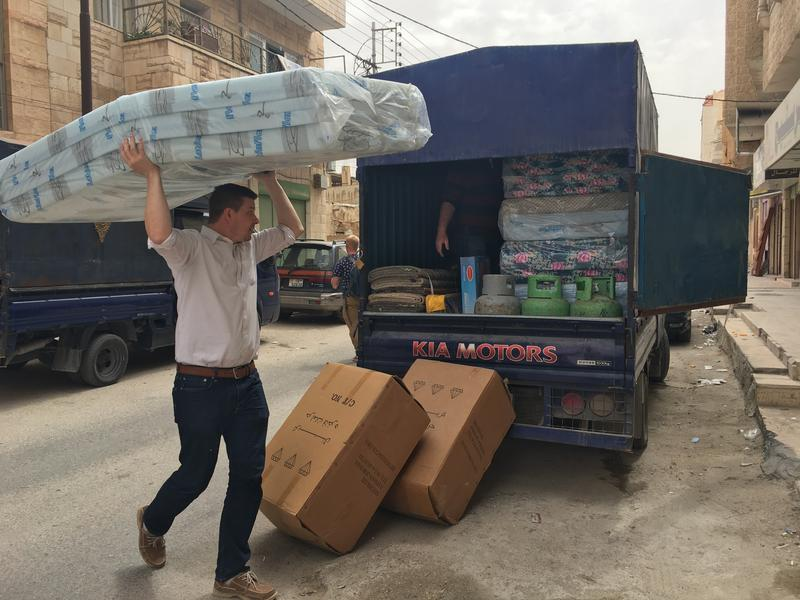 Ethan Anderson offloads a mattress and supplies in Mafraq, Jordan. The supplies were purchased with money from the couple's fundraising campaign.