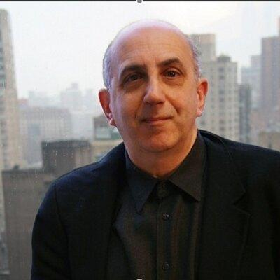 Man who's bald wearing black jacket, black shirt, and black tie with tall city buildings in background
