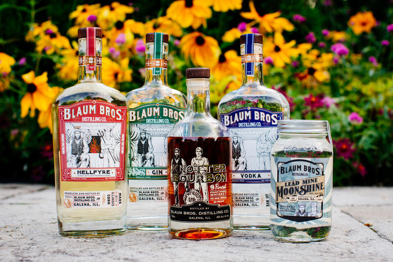 Five bottles of liquor featuring Blaum Bros. labels, with yellow, black-eyed susan flowers behind them