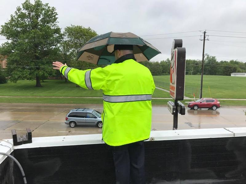 A Moline Police officer waves to cars from the rooftop of a Dunkin' Donuts.