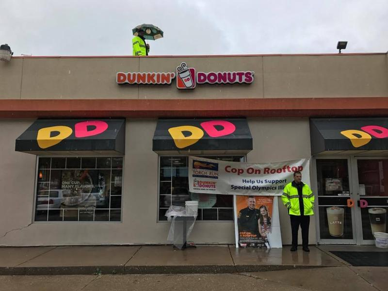 A Moline Police officer stands atop a Dunkin' Donuts as another officer stands below to collect donations for Illinois' Special Olympics.
