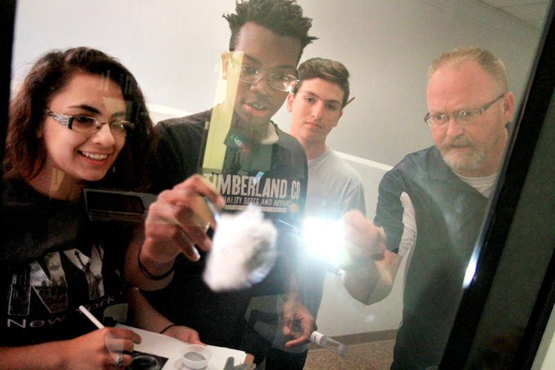 From left: Galesburg High School students Faby Chavez, Trevon Lee, and David Olivas dust and lift fingerprints with the help of Dave Kellogg, coordinator and instructor of criminal justice at Carl Sandburg College