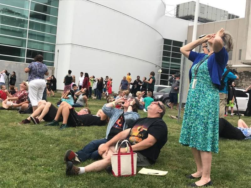 Spectators watch the eclipse from the lawn of the Putnam Museum
