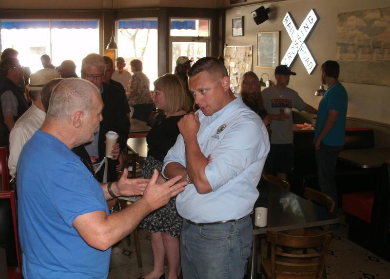 IL State Senator Neil Anderson (R) listens to a man at Theo's Java Club, Rock Island, IL.