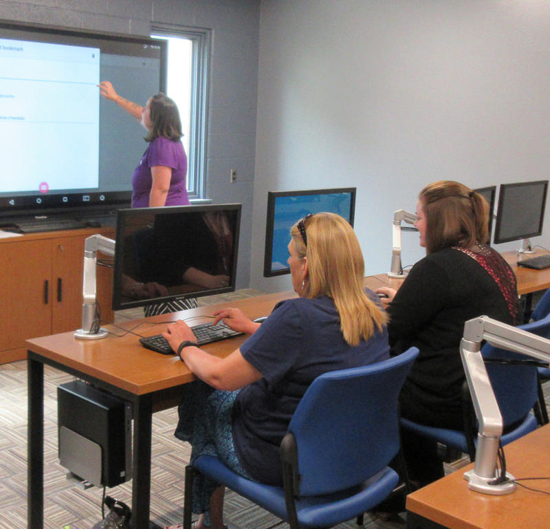 A woman uses a very large touchscreen while two others work at their computers.