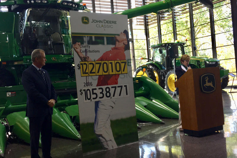 Tournament Director Clair Peterson (left) and volunteer coordinator Pat Shouse announce this year's fundraising total for Birdies for Charity at Deere and Company Headquarters.
