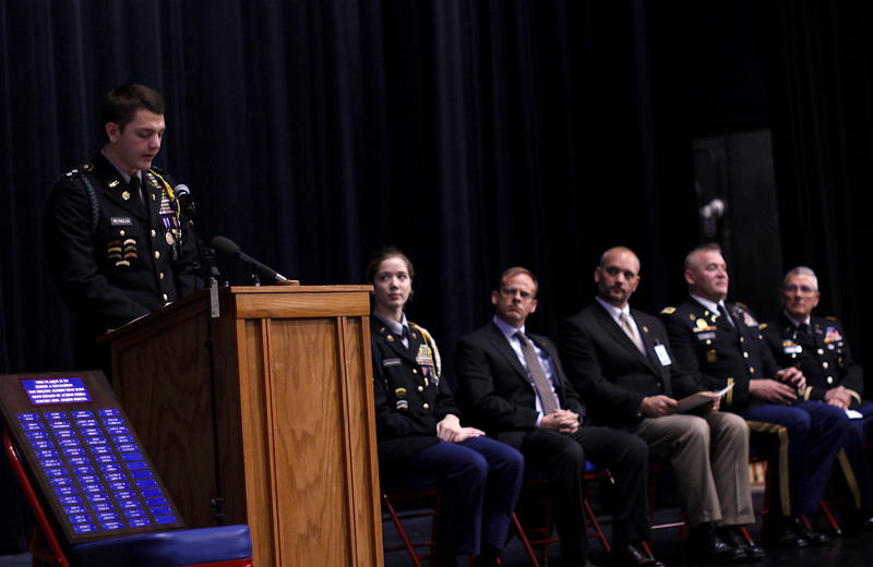 ROTC Student Sam Reynolds speaks at Davenport Central High School's Fallen Warrior Ceremony. The plaque to his left contains the names of Davenport Alumni who were killed in action.