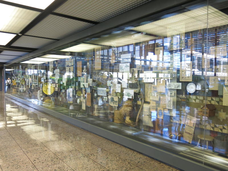 Photo of a wall of glass cases containing items such as print ads and tools.