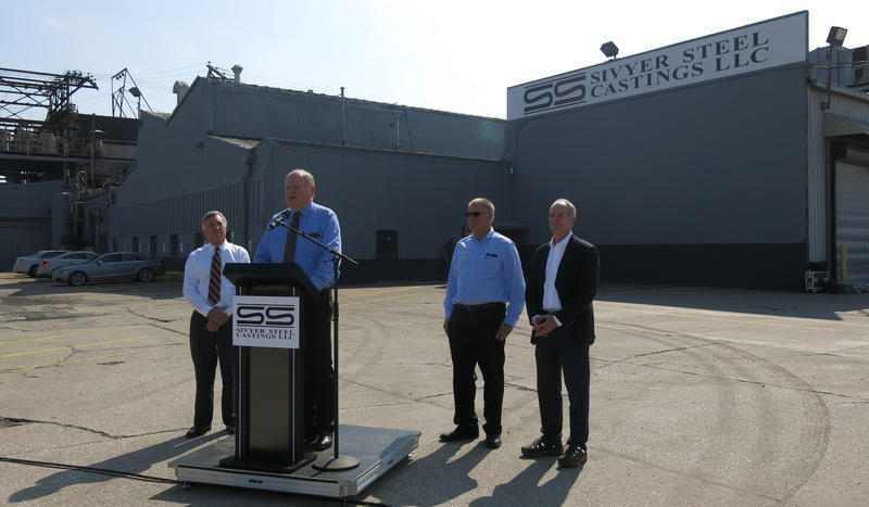 Pres. Keith Kramer (L), CEO Mike Baxley (at podium), Joel Lorentzen (2nd from R), and Scott Tinsman (R)
