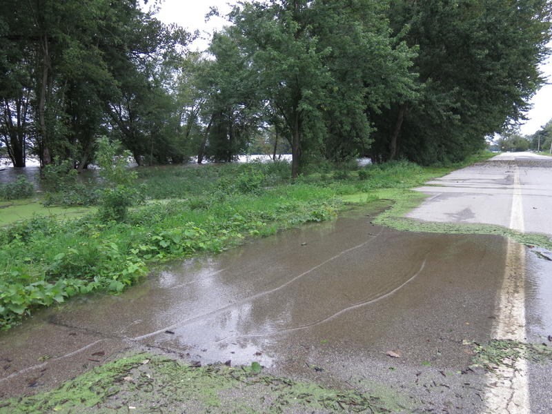 """Beyond the """"road closed"""" barrier, small waves of water reach the road to Credit Island."""