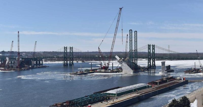 Screenshot from a webcam in Bettendorf, Iowa. The brighter white rectangular piece on the angled large, gray pier (right) is the first steel part of the bridge arch to be attached.